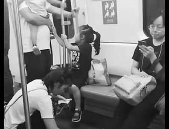 地铁上小孩不慎将水洒在地板上,妈妈擦拭水渍之举被拍友捕捉传上网