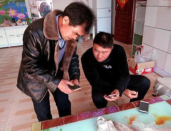 邵胡同北村委会工作人员正在向辖区村民普及宣传《学习强国APP》